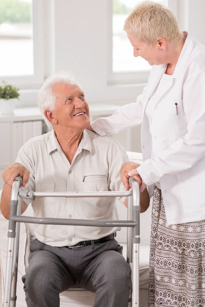 Clinician smiles at elderly patient with walker