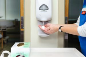 Healthcare worker applies hand sanitizer from wall mounted dispenser