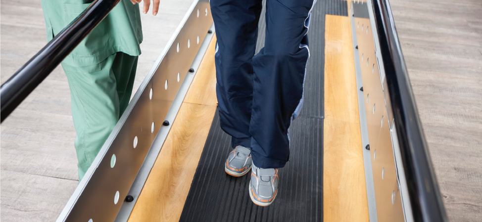 Paatient moves across gait anaylsis platform accompanied by clinician
