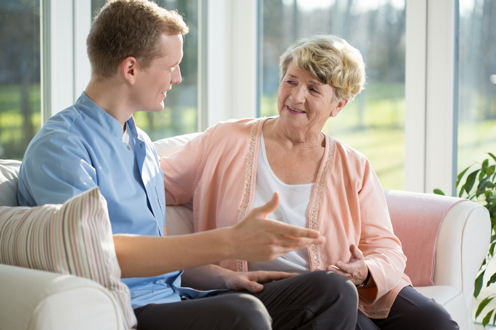 Young man and senior woman sit on couch discussing