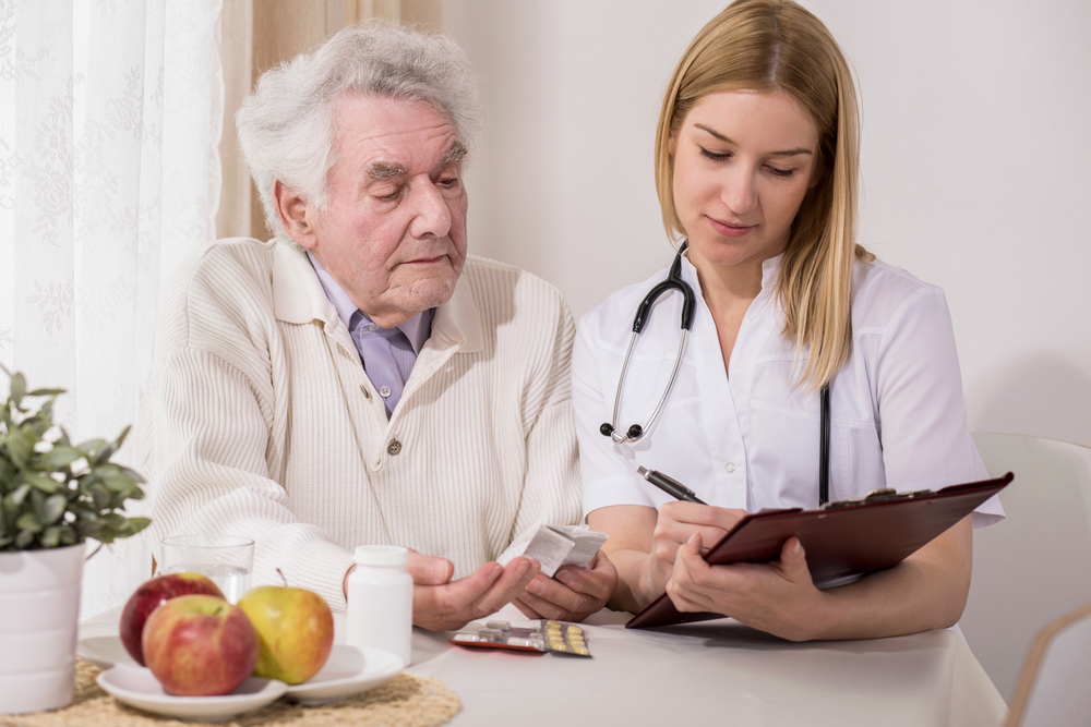 Elderly man sits with healthcare professional with clipboard