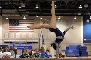 American Female Gymnast Tumbling on Balance Beam