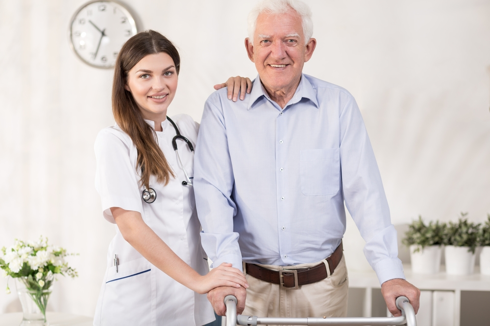 Female clinician stands next to smiling elderly ale patient with walker