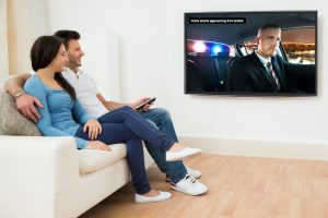 Couple happily watches television with closed captioning on.