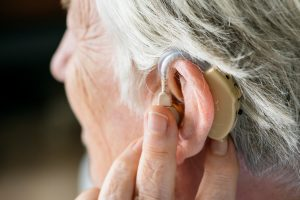 An older adult adjusts their hearing aid in their ear.