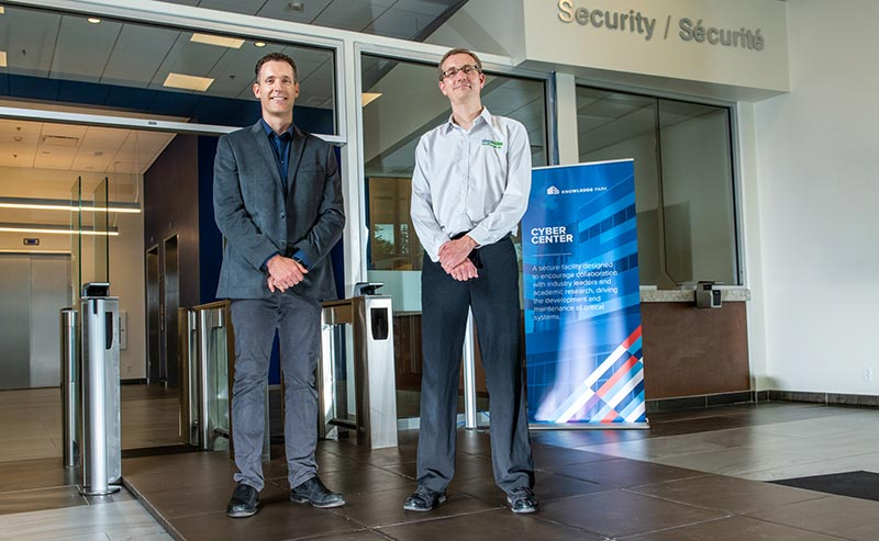 Two Doctors stand on new biometric tiles installed at the new Cyber Centre facility in Fredericton